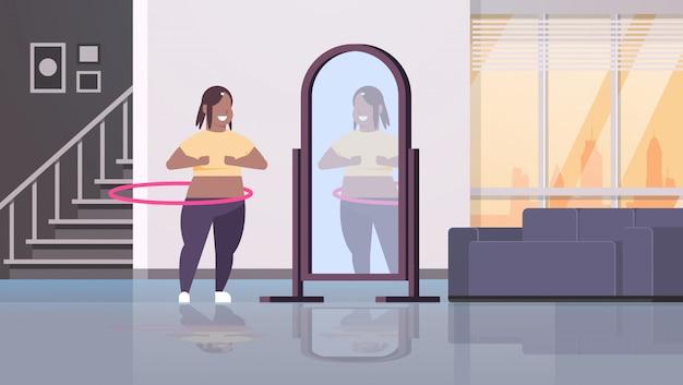 Mulher fazendo ginástica rotativa treino com bambolê, olhando para o reflexo no conceito de espelho menina