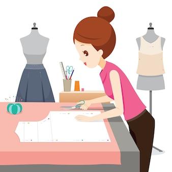Mulher fazendo padrão de roupas, ela usa tesoura para cortar tecido