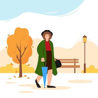 Mulher feliz com guarda-chuva caminhando no parque outono