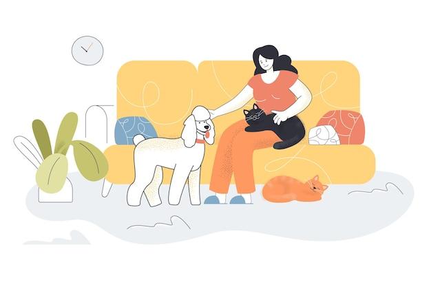 Mulher feliz dos desenhos animados sentada no sofá com animais de estimação