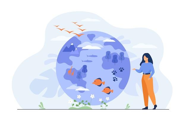 Mulher feliz em pé e apontando no globo com ilustração plana de diversidade de flora e fauna.