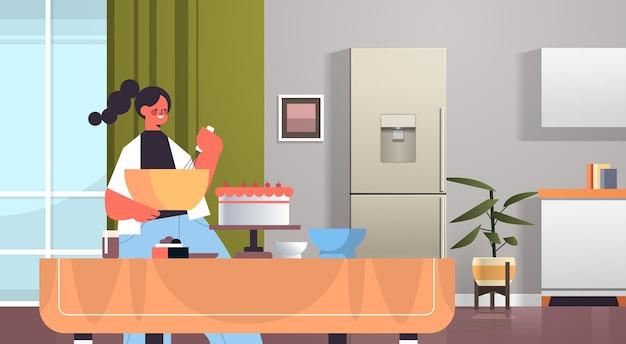 Mulher feliz preparando bolo doce em casa cozinha conceito moderno interior retrato horizontal