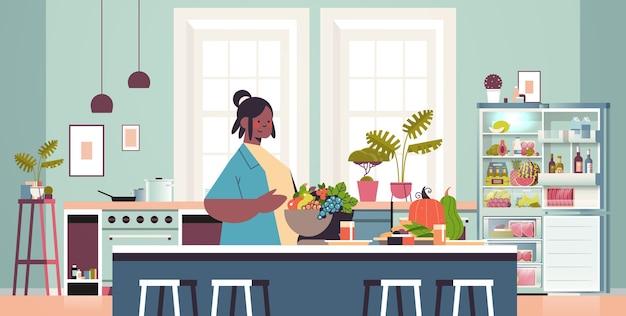 Mulher feliz preparando comida saudável em casa cozinha conceito moderno interior retrato horizontal