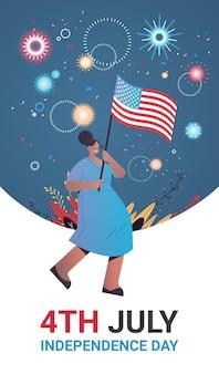 Mulher feliz segurando a bandeira dos estados unidos e comemorando o feriado do dia da independência americana, banner vertical de 4 de julho
