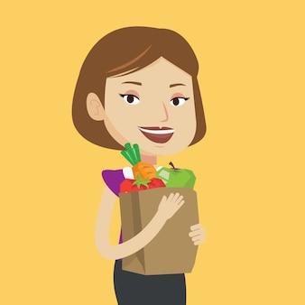Mulher feliz, segurando o saco de compras de supermercado.