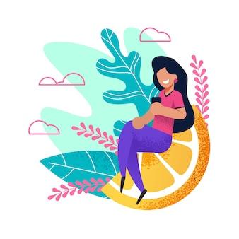 Mulher feliz senta-se na enorme fatia de laranja com telefone