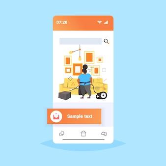 Mulher gorda usando aspirador feminino afro-americano zelador em uniforme aspirar sofá fazendo tarefas domésticas serviço de limpeza conceito smartphone tela on-line app móvel app esboço de comprimento total