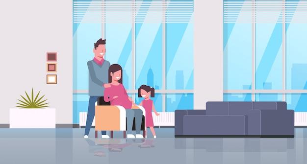 Mulher grávida com marido e filha