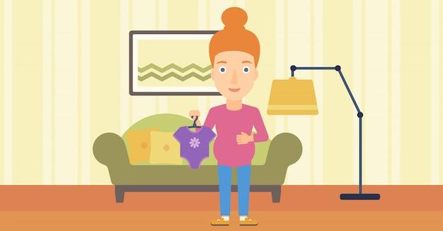 Mulher grávida com roupas para o bebê.