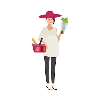 Mulher grávida elegante e sorridente usando chapéu e carregando uma cesta de compras com alimentos saudáveis e produtos saudáveis
