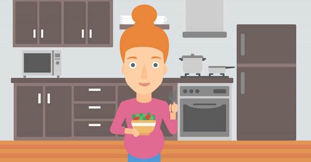 Mulher gravida que come a salada.