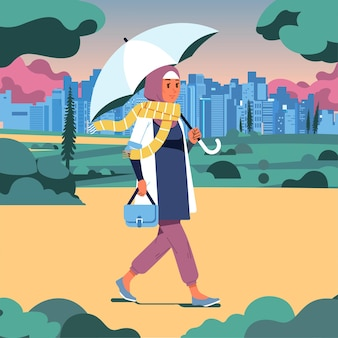 Mulher hijab caminhando no parque segurando um guarda-chuva em um dia nublado