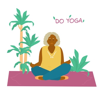 Mulher idosa africana sorridente meditando na esteira de ioga rodeada de plantas.
