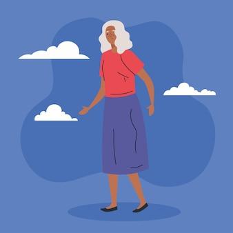 Mulher idosa bonita caminhando sobre fundo azul.
