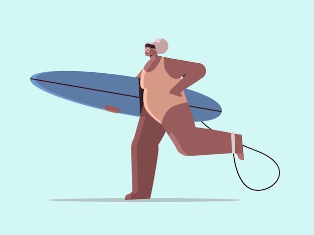 Mulher idosa com prancha de surf envelhecida surfista afro-americana segurando uma prancha de surfe, férias de verão, conceito de velhice ativa