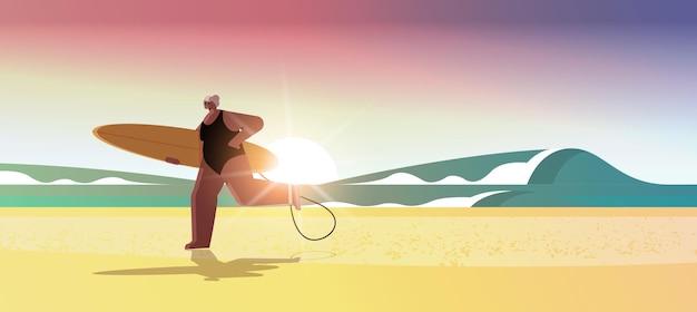 Mulher idosa com prancha de surfe, surfista, segurando uma prancha de surfe, férias de verão, conceito de velhice ativa
