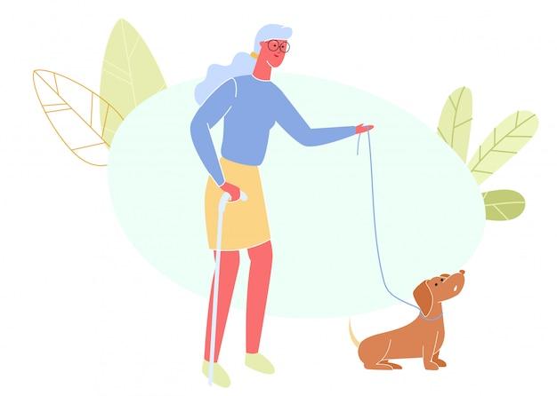 Mulher idosa com vara de passeio e cão na trela.