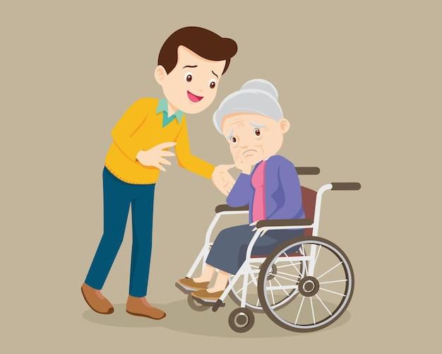 Mulher idosa senta-se em uma cadeira de rodas e o filho carinhosamente coloca as mãos em seus ombros. homem cuida da mãe
