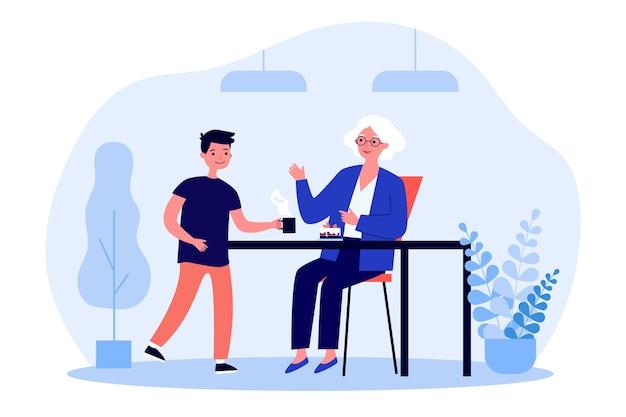 Mulher idosa sentada à mesa e o neto servindo chá para ela