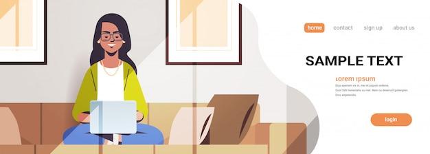Mulher indiana bonita sentada no sofá usando a garota do laptop trabalhando em casa freelance conceito moderno sala interior horizontal comprimento total cópia espaço