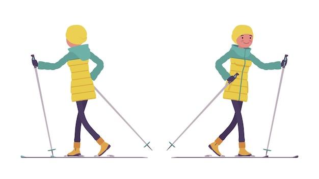 Mulher jovem com uma jaqueta brilhante gosta de viajar sobre a neve em esquis