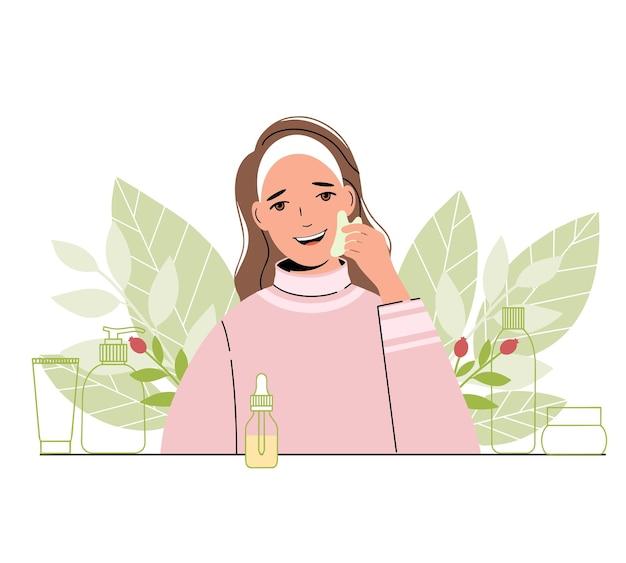 Mulher jovem cuida do rosto ela usa o raspador gua sha jade para massagem