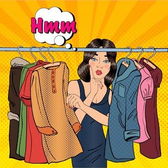Mulher jovem e bonita escolhendo roupas em seu guarda-roupa.