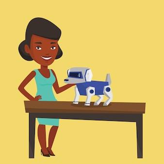 Mulher jovem feliz, brincando com cachorro robótico.