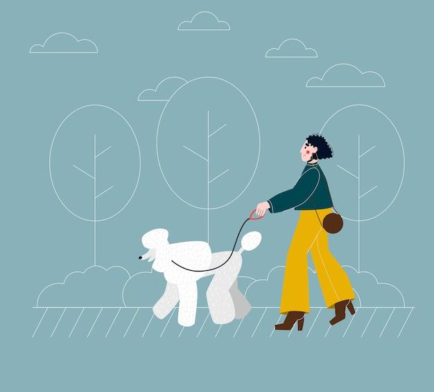Mulher jovem passeando com um poodle de raça de cachorro na cidade