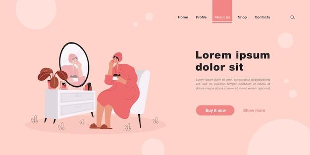 Mulher jovem sentada em frente ao espelho lavando, limpando ou hidratando a pele do rosto. página inicial em estilo simples.