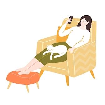 Mulher jovem sentada em uma cadeira amarela com apoio para os pés usando smartphone e gato branco. ilustração aconchegante