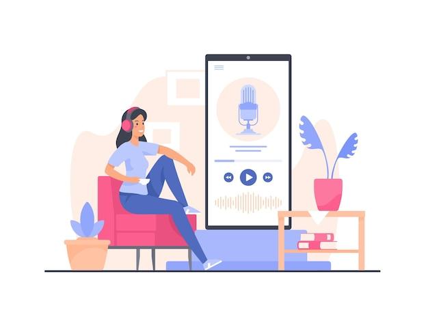 Mulher jovem sentada em uma poltrona confortável em casa ouvindo a gravação de podcast usando o smartphone
