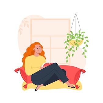 Mulher jovem sentada perto da janela lendo um livro, relaxando em casa