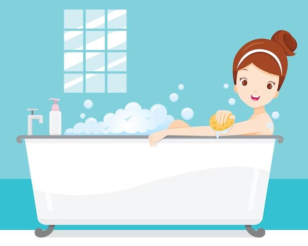 Mulher jovem tomando banho na banheira com espuma de sabão