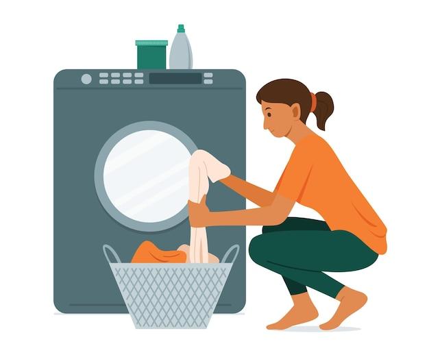 Mulher lava a roupa com máquina de lavar