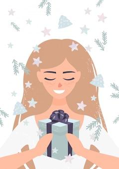 Mulher loira sorridente segurando um presente de natal