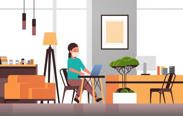 Mulher na máscara protetora usando o laptop conceito de quarentena de pandemia de coronavírus trabalho em casa educação online freelance moderna sala de estar interior comprimento total horizontal