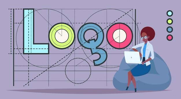 Mulher negócio, trabalhando, ligado, computador laptop, sobre, logotipo, palavra, criativo, desenho gráfico