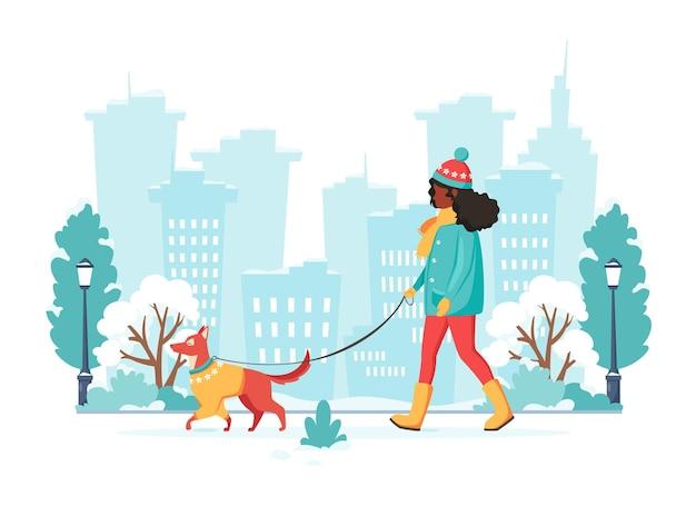 Mulher negra andando com cachorro em cidade de inverno