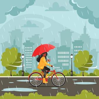 Mulher negra andando de bicicleta sob um guarda-chuva durante a chuva. chuva de outono. atividades ao ar livre de outono.