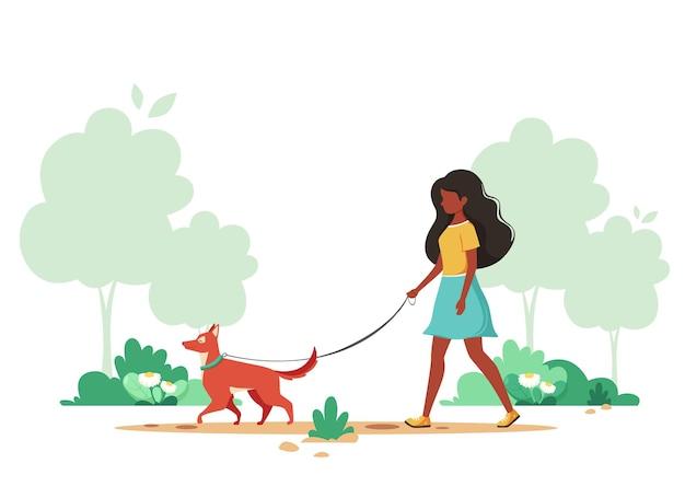 Mulher negra caminhando com cachorro na primavera atividades ao ar livre
