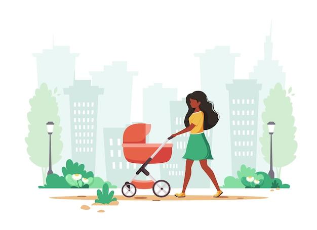 Mulher negra caminhando com carrinho de bebê na primavera