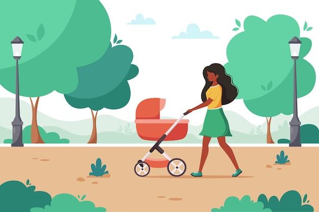 Mulher negra caminhando com carrinho de bebê no parque da cidade