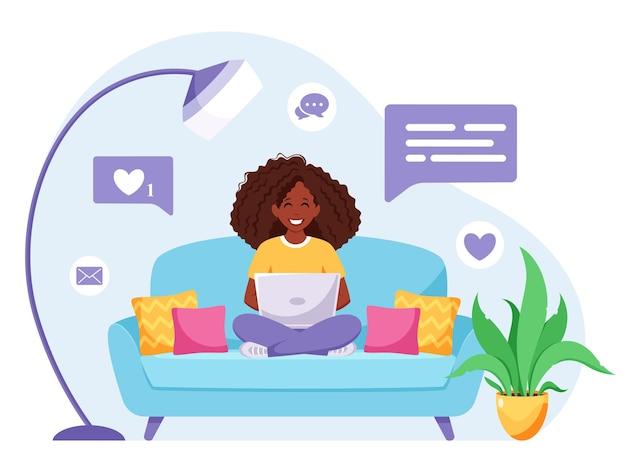 Mulher negra sentada em um sofá e trabalhando no laptop. freelancer, home office