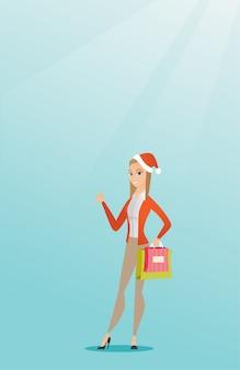 Mulher no chapéu de santa que compra presentes do natal.