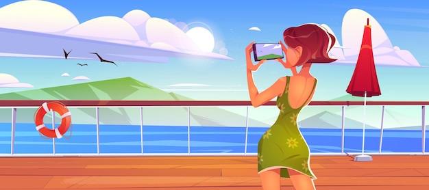Mulher no convés do cruzeiro fotografando a paisagem marinha