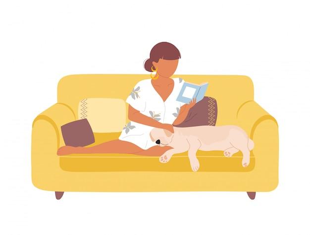 Mulher no sofá lendo livro e acariciando o cão