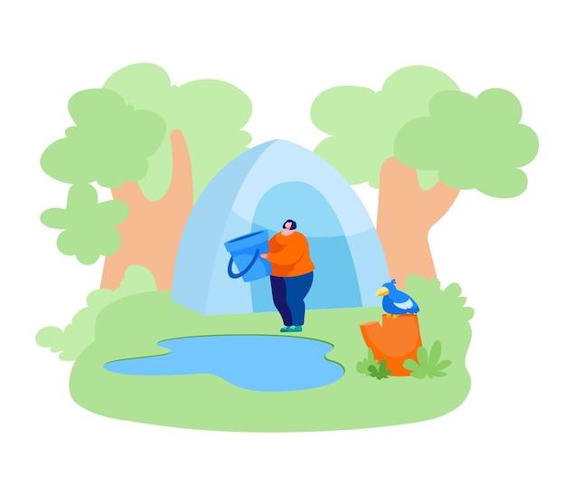 Mulher parada com balde perto da lagoa da floresta indo buscar água