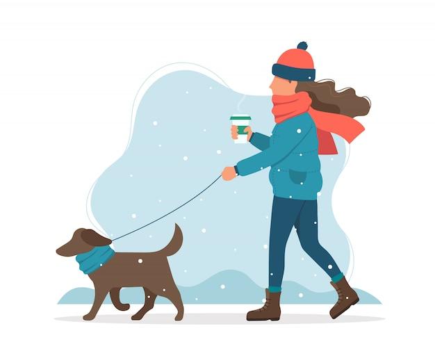 Mulher passeando com um cachorro no inverno.