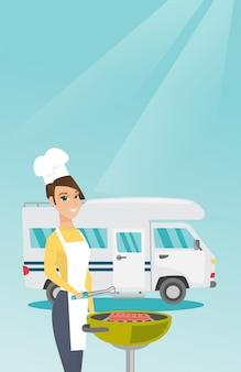 Mulher que assa a carne na frente da camionete de campista.